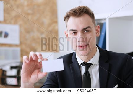 Smiling Businessman in suit hold in hand blank calling card closeup. White collar partners company name exchange executive or ceo introducing at conference product consultant sales clerk concept