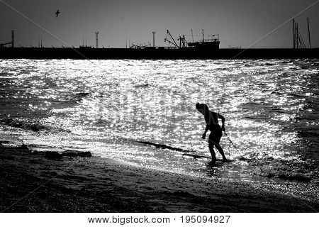 Silhouette of a child emerging from the sea in the background of the port Russia
