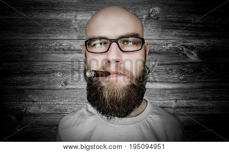 A man with glasses and a cigar against a wooden wall Face