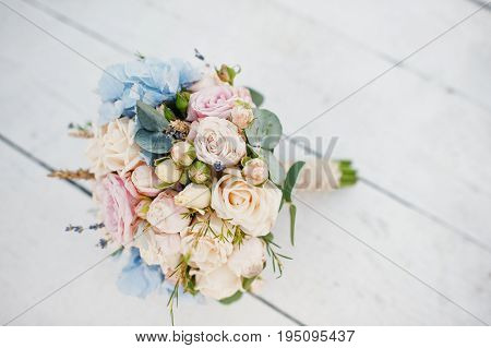 Amazing Wedding Bouquet Made Of Roses, Hydrangeas And Lavender Laying On The White Wooden Ground.