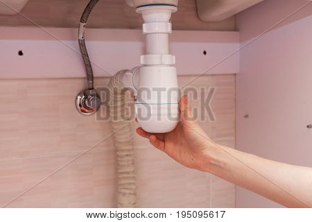 Clearing of blocked hammered polluted plastic U siphon for wash basin sanitary devices plumbing fixtures special means cleanser. Plumbing siphon. White plumbing siphon assembly.