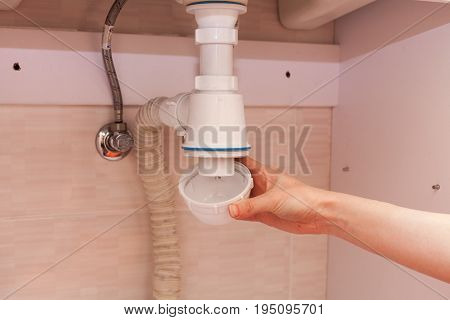 Clearing of blocked hammered polluted plastic U siphon for wash basin sanitary devices plumbing fixtures special means cleanser. Plumbing siphon. White plumbing siphon assembly