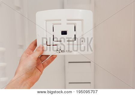 Installing new clean air filter in an empty washed refrigerator. Young woman cleaning refrigerator