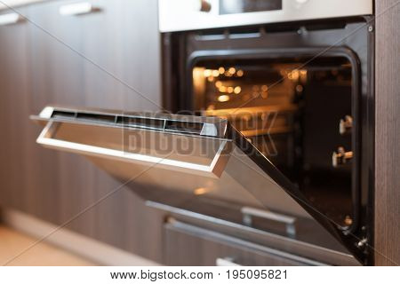 Empty open electric oven with hot air ventilation. New oven. Door is open and light is on