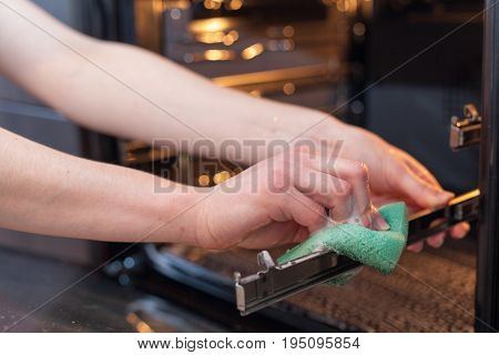 Housework and housekeeping concept. Scrubbing the stove and oven. Close up of female hand with green sponge cleaning the kitchen oven