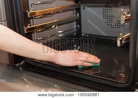 Housework and housekeeping concept. Scrubbing the stove and oven. Female hand with green sponge cleaning the kitchen oven.