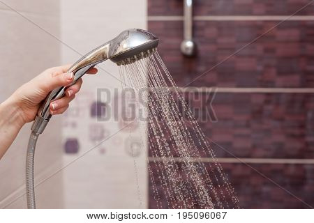 Water streams flow out of working shower head right down
