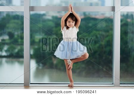 Full length portrait of talented little girl in blue tutu skirt practicing ballet at class, panoramic windows on background