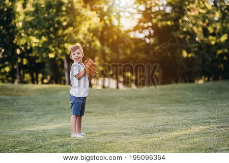 Full-lenght image of cute little boy playing baseball on lawn and smiling