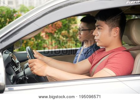 Profile view of confident young man wearing red T-shirt giving his best friend a lift, head and shoulders portrait
