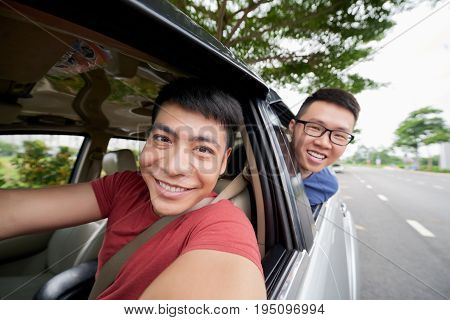 Waist-up portrait of handsome Vietnamese man taking selfie with best friend while driving car