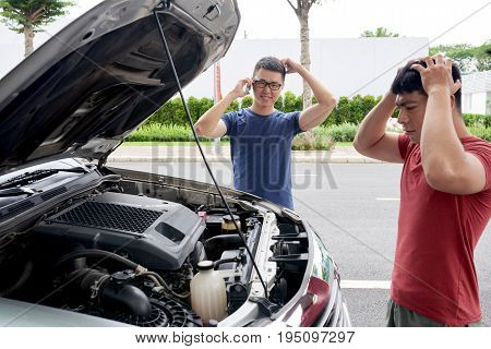 Profile view of shocked Asian man looking under hood of car in order to find cause of breakage while his friend calling to roadside assistance