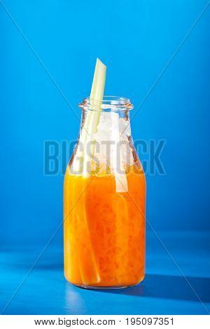 Summer Lemonade - Sea Buckthorn Lemonade decorated with Celery. Lemonade Glass Bottle on Bright Blue Background