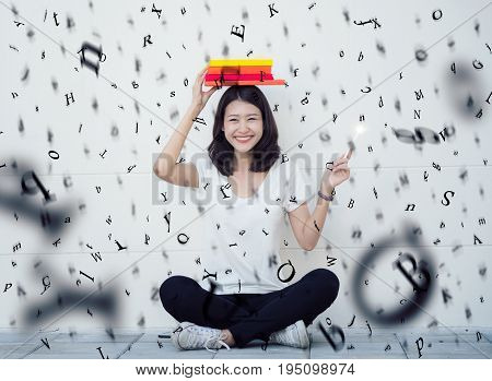 Asian lady sitting with a book and rain of alphabet student university and knowledge concept.