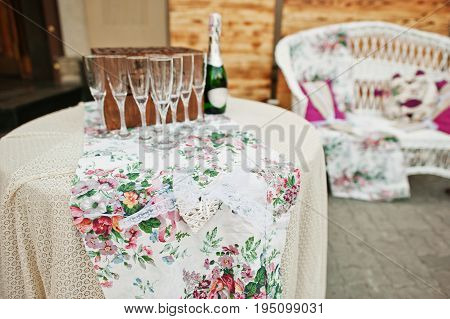 Beautiful Wedding Champagne Glasses And A Bottle On A Decorated Table.