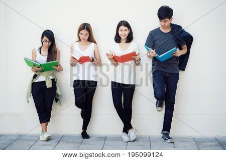 Asian student read a book in university people group stand friend in university.