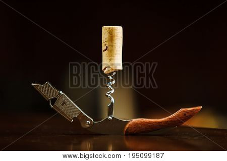 Wooden cork in a corkscrew lies on table. Bottle opener isolated photo. Metallic device with wooden handle for opening alcoholic drinks