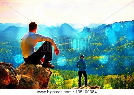 Film grain effect. Boy and girl tourists stay on cliff and thinking. Dreamy fogy landscape blue misty sunrise in a beautiful valley below