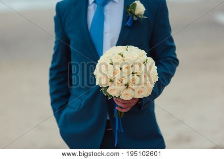 Wedding Groom With Bride's Bouquet Of Flowers Outside