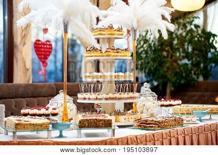 Shot of a restaurant table with plenty of different tasty desserts cupcakes and creamy cakes sweet sugar eating cafe celebration concept.