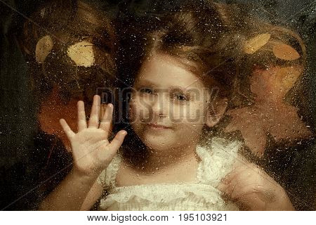 Little caucasian girl close up portrait across a water drops on glass with autumn leaves in background. Emotional portrait autumn concept.