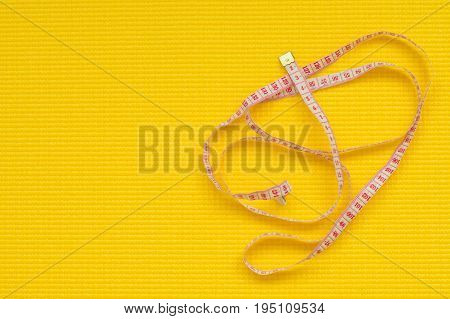 Long tapeline on yellow yoga matt. Weight loss concept. Fitness concept
