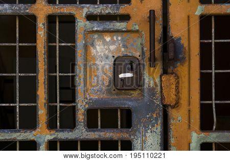 Locked in or locked out? Old paint peeling rusting locked metal security door.