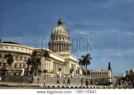 The Beautiful Capitol Building Of Cuba In Havana with people on the street.