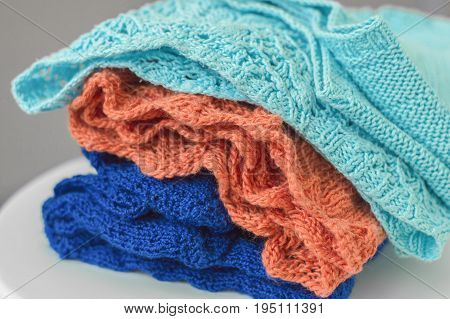 Pile of knitted fabric. Knitwear of light blue orange and dark blue color
