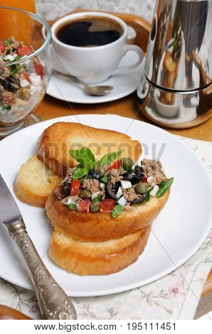 Breakfast from fried toast with chopped tuna with egg cubes of tomatoes and olive slices capers with a cup of coffee a coffee pot on a tray