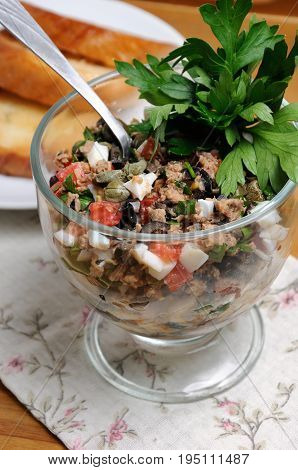 Chopped tuna with egg cubes of tomatoes and olive slices capers and parsley. Salad in a glass.