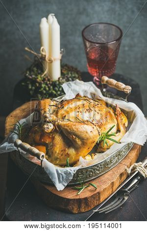 Christmas table set with roasted whole chicken stuffed with oranges, bulgur and rosemary, decorative candles and glass of rose wine, grey concrete wall background. Selective focus, Slow food concept