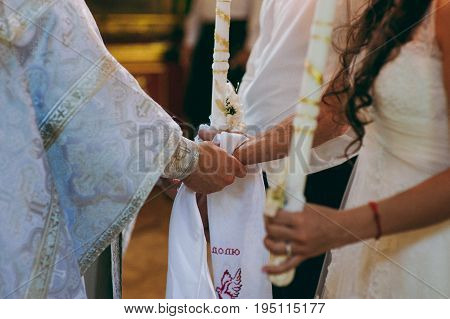 Hands Of Bride And Groom Tied Wedding Towels. The Priest Binds The Bride's Hand Towel. Hands Of Youn
