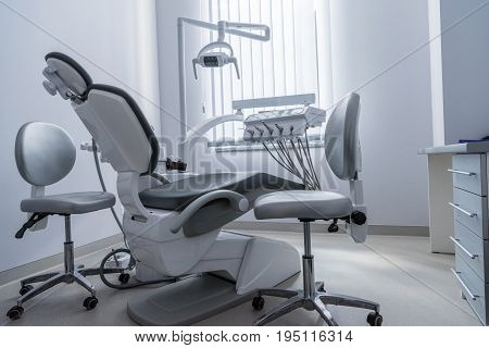 Empty Dentist Office With Chair And Various Dental Equipment