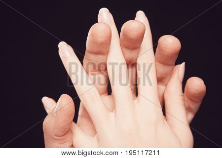 Closeup of couple hands with fingers interlocked together against black background
