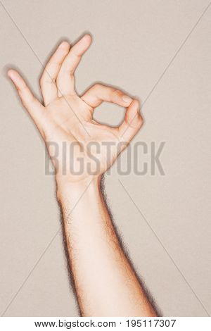 Closeup of a hand making okay sign against gray background