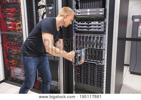 Mid adult male computer engineer installing blade server in chassis at datacenter
