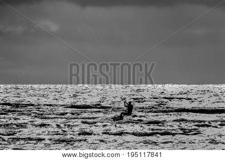 Kite boarding. Kitesurf freestyle at sunset. Black and white.