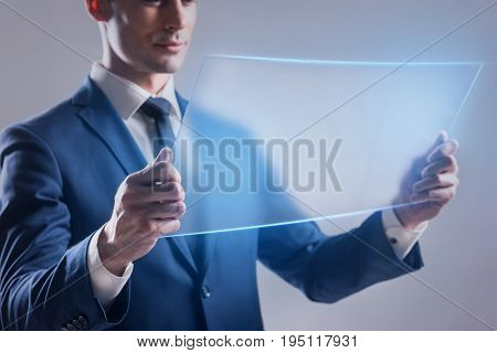 Business technology internet and network concept. Successful young man is looking at transparent display with concentration