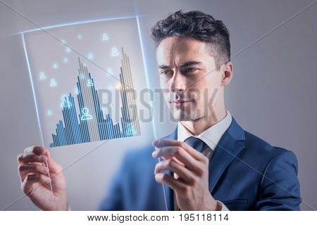 Modern virtual technology concept. Elegant young businessman is looking at transparent screen with concentration while managing users
