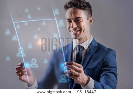 World social media network connection concept. Joyful young businessman is looking at transparent screen with smile while managing users