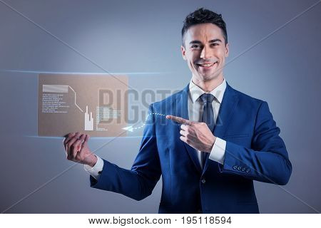 Look here. Portrait of young man in suit is expressing cheerfulness while showing tablet and pointing to diagram. He is looking at camera with joy