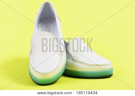 Pair Of Female Leather Shoes Isolated On Lemon Yellow Background