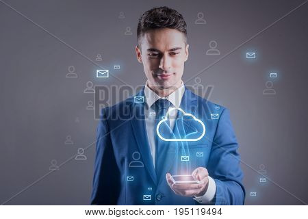 Sharing information concept. Delighted businessman is exchanging messages with members of his address book via cloud storage. He is holding smartphone and looking at screen with smile