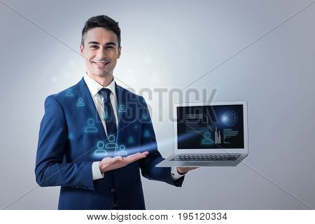 Global communication concept. Joyful energetic young businessman is standing with laptop and demonstrating screen with chart of users connection while looking at camera with happiness