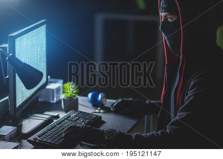 Poor protection system. Profile of concentrated computer burglar in mask is downloading private information while sitting at table