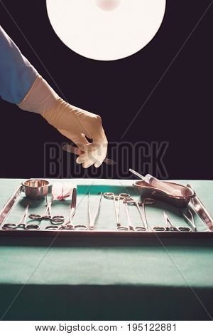 Closeup of a surgeon's hand reaching for medical equipment in operating theatre