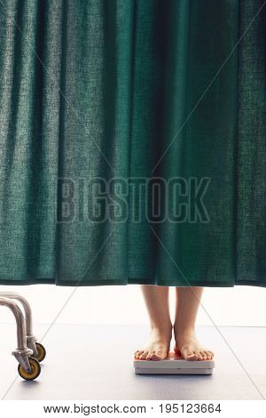 Person on weighing scales behind curtain in hospital