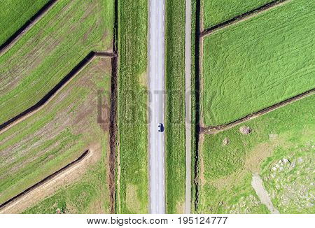 Aerial of a car driving along a rural road