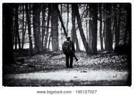 Vintage Black And White Photo Of Photographer Walking On Path In Forest.